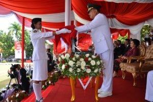 Gubernur sebagai Inspektur Upacara peringatan Hari Kemerdekaan RI ke-71 sedang menyerahkan bendera merah putih kepada Christi Mamoleh siswi SMA I Manado